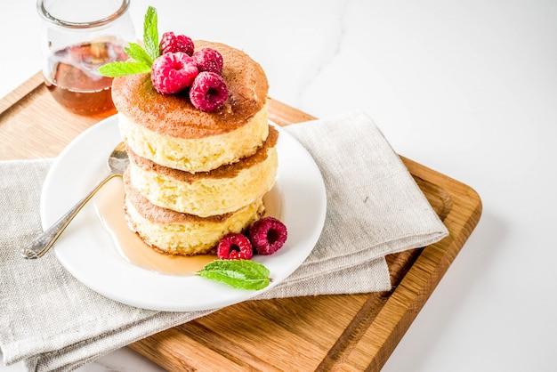 Comida asiática de moda, panqueques soufflé de japón esponjoso, hotcakes con jarabe de arce y mesa de concreto ligero de frambuesa
