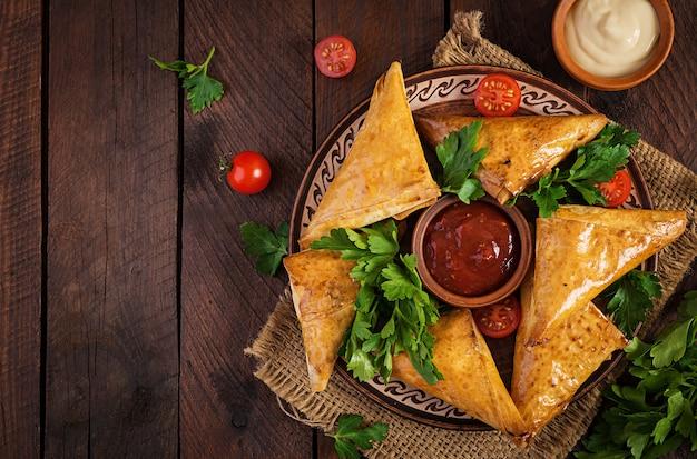 Comida asiática. samsa (samosas) con filete de pollo y queso en madera.