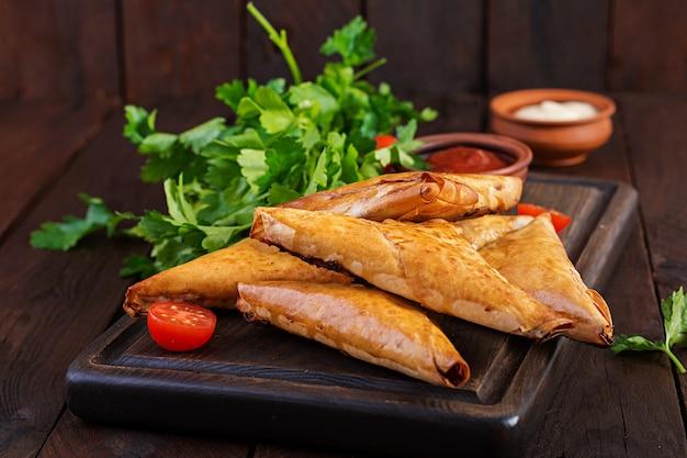 Comida asiática. samsa (samosas) con filete de pollo y queso.