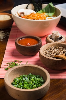 Comida asiática con tazón de madera de cebolla tierna y semillas de cilantro con salsa.