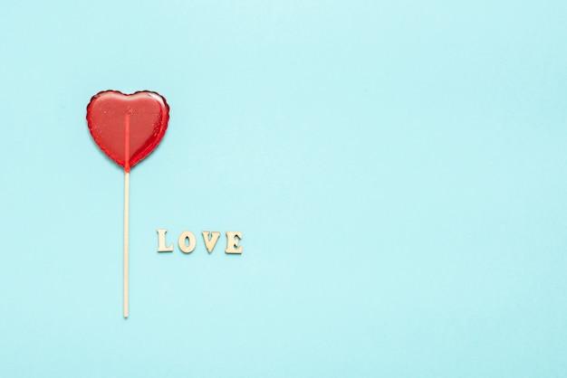 Comida y bebida, concepto de vacaciones. piruleta en forma de corazón para el amor día de san valentín con fondo azul. copia espacio