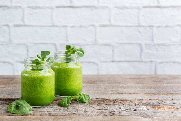 Comida y bebida, dieta y nutrición saludables, estilo de vida, vegano, alcalino, concepto vegetariano. batido verde con ingredientes orgánicos, verduras en una mesa de cocina de madera. copiar el fondo del espacio