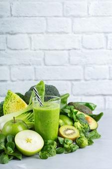 Comida y bebida, dieta y nutrición saludables, estilo de vida, vegano, alcalino, concepto vegetariano. batido verde con ingredientes orgánicos, verduras en una mesa de cocina moderna. copiar el fondo del espacio