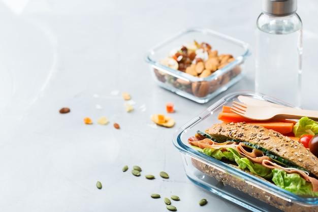 Comida y bebida, naturaleza muerta, dieta y nutrición, alimentación saludable, concepto para llevar. fiambrera con bocadillo, frutas, verduras, mix de frutos secos y botella de agua. copiar el fondo del espacio