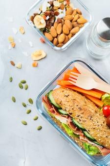 Comida y bebida, naturaleza muerta, dieta y nutrición, alimentación saludable, concepto para llevar. fiambrera con bocadillo, frutas, verduras, mix de frutos secos y botella de agua. vista superior de fondo plano laico
