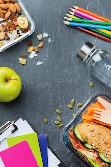 Comida y bebida, naturaleza muerta, dieta y nutrición, alimentación saludable, concepto para llevar. fiambrera escolar y material de oficina. vista superior plana endecha, fondo de pizarra de espacio de copia