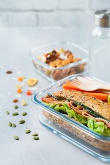 Comida y bebida, naturaleza muerta, dieta y nutrición, alimentación saludable, concepto para llevar. fiambrera con sándwich, frutas, verduras, mezcla de frutos secos y botella de agua