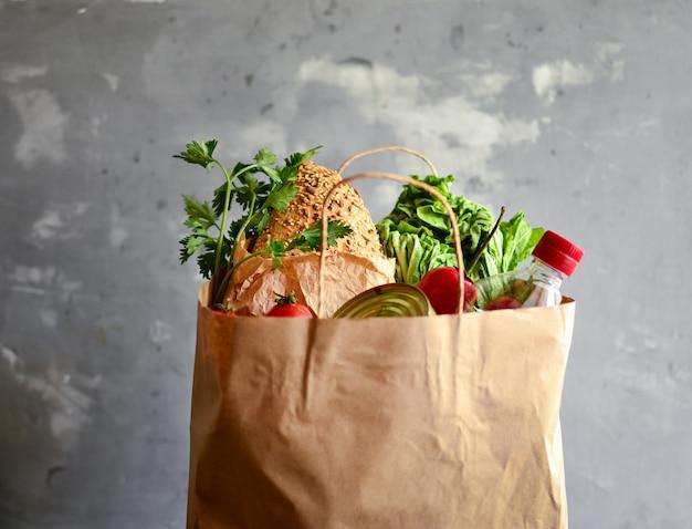 Comida en una bolsa de papel. donación de alimentos o concepto de entrega de alimentos. aceite, pan, repollo, ensalada, verduras, comida enlatada.