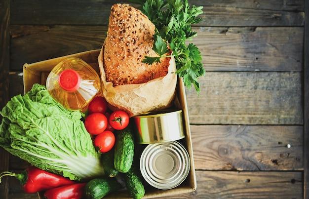 Comida en una caja de cartón. donación de alimentos o concepto de entrega de alimentos. aceite, repollo, ensalada, verduras, comida enlatada. vista superior