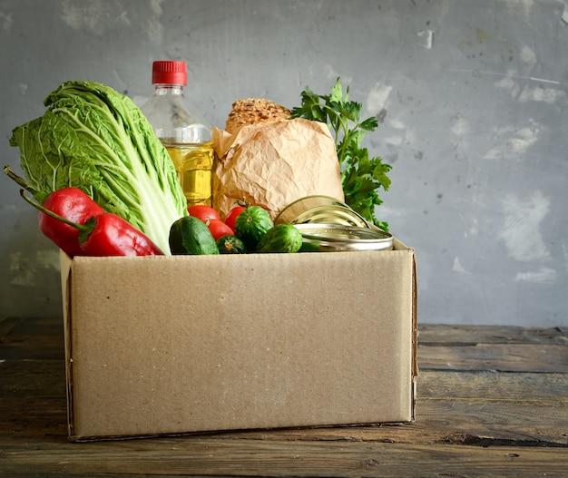 Comida en una caja de cartón. donación de alimentos o concepto de entrega de alimentos. aceite, repollo, ensalada, verduras, comida enlatada.