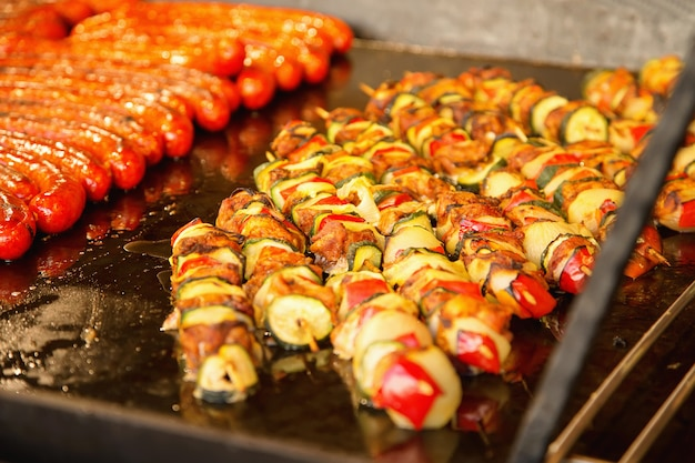Comida de la calle. las salchichas de cerdo y los kebabs se fríen en grandes bandejas para hornear en la calle.