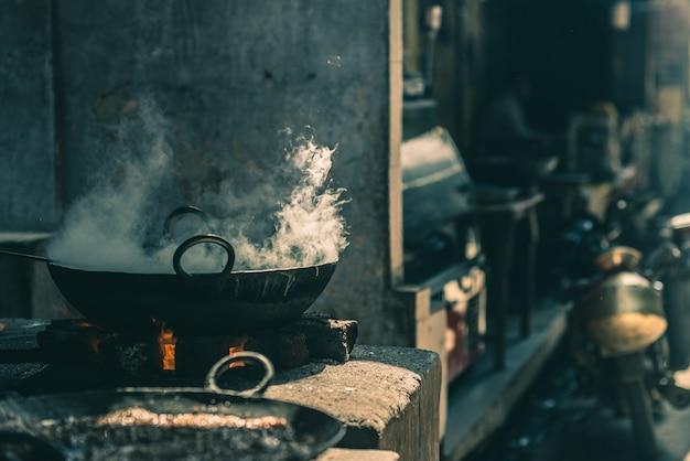 Comida callejera en la india cocinando en una gran sartén fatiscente o wok en un pequeño puesto de comida callejera.