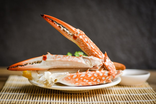 Comida de cangrejo hervida en un plato blanco y salsa de mariscos en la mesa