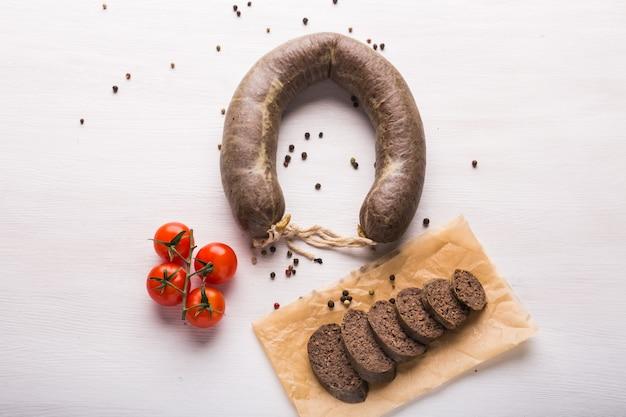 Comida, carne y delicioso concepto: embutidos elaborados con carne de caballo con especies y verduras.
