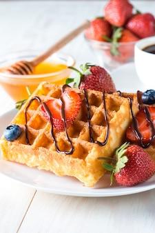 Comida casera fresca de baya gofres belgas con miel, chocolate, fresa, arándano, jarabe de arce y crema. concepto de desayuno de postre saludable con jugo