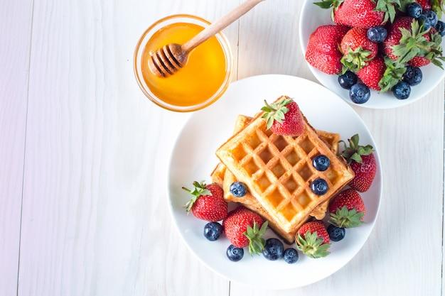 Comida casera fresca de bayas gofres belgas con miel