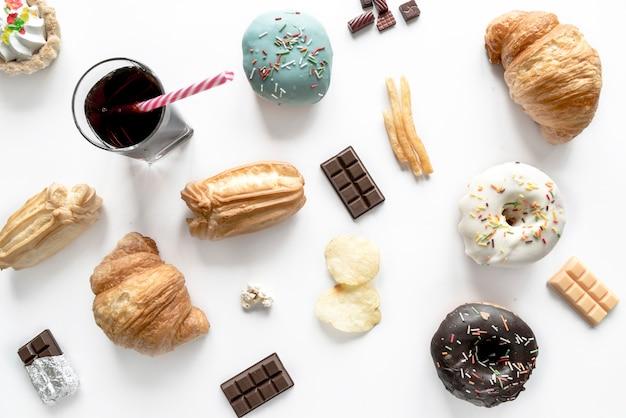 Comida chatarra con barra de chocolate y bebida fría aislada sobre superficie blanca