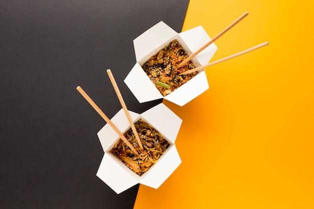 Comida china para llevar con palillos.