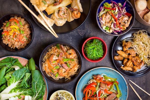 Comida china sobre fondo negro. fideos, arroz, albóndigas, pollo salteado, dim sum, rollitos de primavera