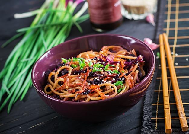 Comida china. los tallarines del sofrito del vegano con la col roja y la zanahoria en un cuenco en un fondo de madera negro.