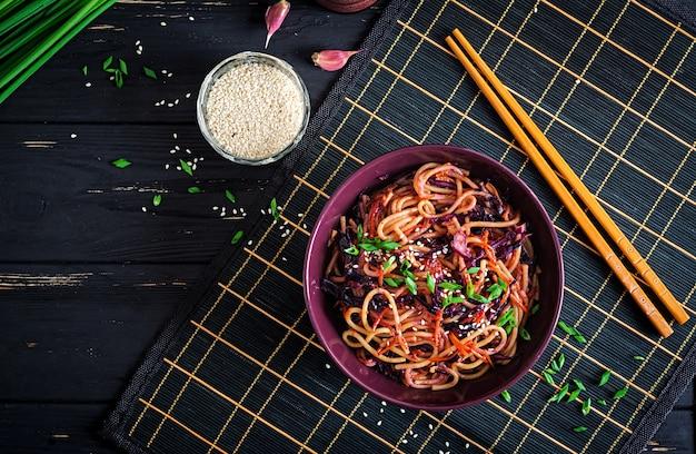 Comida china. vegano salteado de fideos con col roja y zanahoria en un recipiente sobre un fondo negro de madera. comida de cocina asiática. vista superior