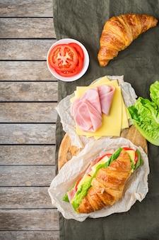 Comida, desayuno, mañana y almuerzo, bricolaje, hágalo usted mismo concepto. sándwich de croissant fresco con ingredientes, jamón, queso, lechuga y tomate en una mesa de madera. endecha plana, copia de fondo del espacio