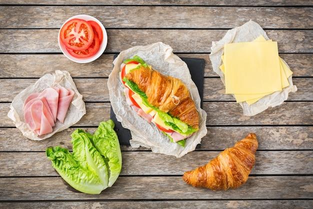 Comida, desayuno, mañana y almuerzo, bricolaje, hágalo usted mismo concepto. sándwich de croissant fresco con ingredientes, jamón, queso, lechuga y tomate en una mesa de madera. fondo plano laico