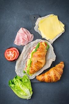 Comida, desayuno, mañana y almuerzo, bricolaje, hágalo usted mismo concepto. sándwich de croissant fresco con ingredientes, jamón, queso, lechuga y tomate sobre una mesa. fondo plano laico