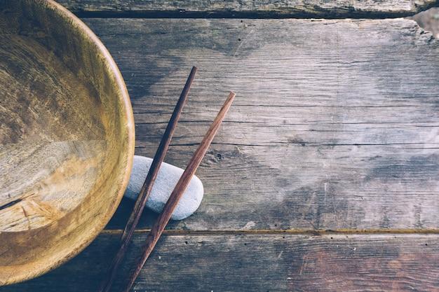 Comida desintoxicante con cuenco de madera vacío y palillos de madera.