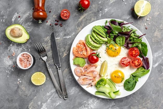 Comida de dieta cetogénica. desayuno con salmón, camarones cocidos, camarones, huevos fritos, ensalada fresca, tomates, pepinos y aguacate. concepto de alimentación saludable. vista superior.