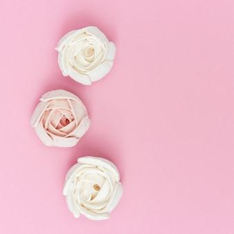 Comida dulce creativa, plana, con malvaviscos rosados y blancos en forma de flor. concepto de vacaciones.