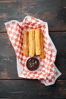 Comida española como churros españoles con chocolate y caramelo en bandeja de papel