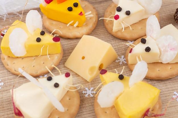 Comida festiva para el año nuevo: el año de la rata blanca. ratones alrededor de un trozo de queso. aperitivo. humor navideño.