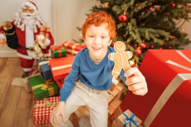 Comida festiva. enfoque selectivo en una sabrosa galleta de jengibre casera sostenida por un lindo niño pelirrojo en traje casual sonriendo alegremente.