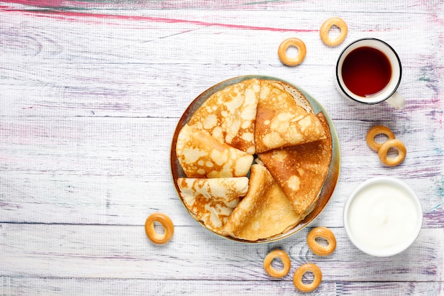 Comida del festival shrovetide maslenitsa. panqueque ruso blini con mermelada de frambuesa, miel, crema fresca y caviar rojo, terrones de azúcar, requesón, bubliks sobre fondo claro