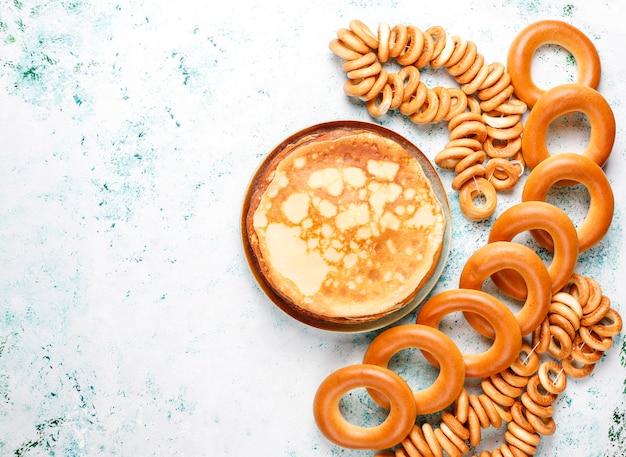 Comida del festival shrovetide maslenitsa. panqueque ruso blini con mermelada de frambuesa, miel, crema fresca y caviar rojo, terrones de azúcar, requesón a la luz