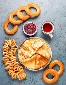 Comida del festival shrovetide maslenitsa. panqueque ruso blini con mermelada de frambuesa, miel, crema fresca y caviar rojo, terrones de azúcar, requesón oscuro
