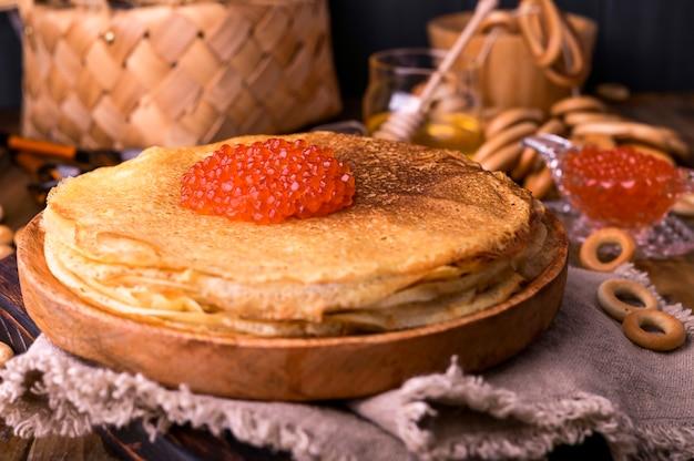 Comida del festival shrovetide maslenitsa week. pila de panqueques rusos con caviar rojo. estilo rústico, espacio libre para texto,