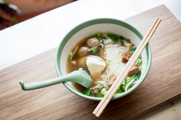 Comida de fideos y sopa con albóndigas y carne de cerdo boild la comida japonesa en el restaurante de tailandia