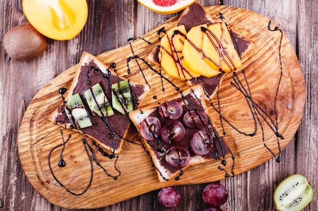 Comida fresca, sabrosa y saludable. ideas para el almuerzo o el desayuno. pan con mantequilla de chocolate, uva.