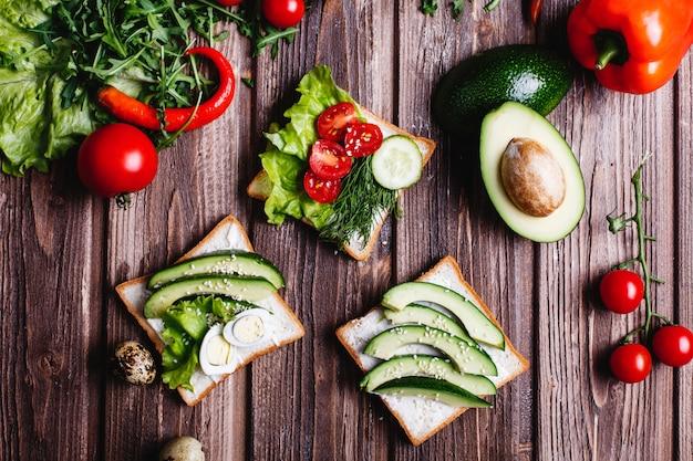 Comida fresca y saludable. ideas de desayuno o almuerzo. pan con queso, aguacate y vegetación.