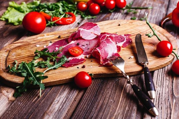 Comida fresca y saludable. rebanadas de carne roja se encuentra en la mesa de madera con rúcula