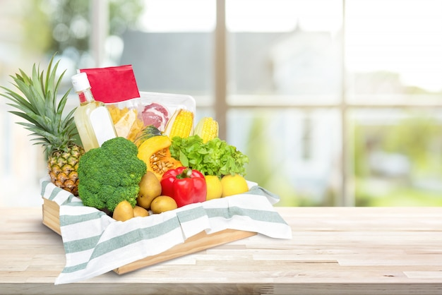 Comida fresca y verduras en caja de bandeja de madera en encimera de cocina