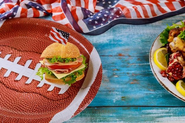 Comida de fútbol americano de juego sobre fondo de madera azul.