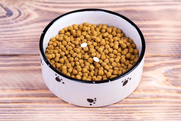 Comida para gatos con dos comprimidos en un recipiente en el suelo