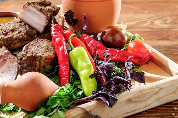 Comida georgiana: platos especiales de carne servidos en un plato de madera con daga tradicional. menú de recetas tradicionales.