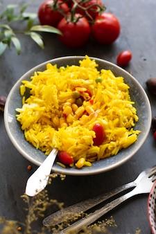 Comida india con arroz, maíz y tomates