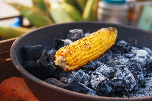 Comida india en la playa: las mazorcas de maíz frescas se asan en las brasas.