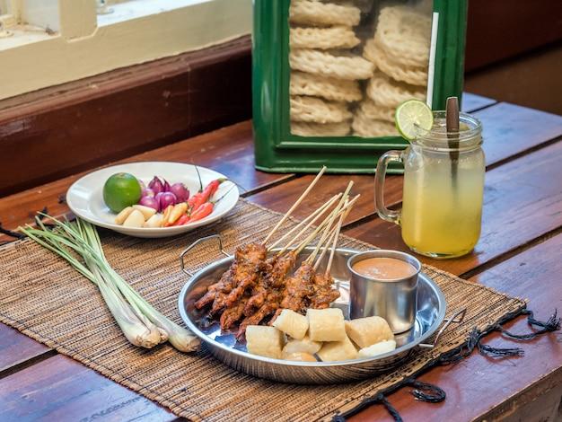 Comida de indonesia satay servida con salsa de maní y rollo de pastel de arroz