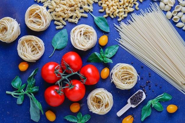 Comida italiana . cocina italiana. ingredientes tomates, tomates cherry amarillos, albahaca fresca, granos de pimienta negra, pasta variada.